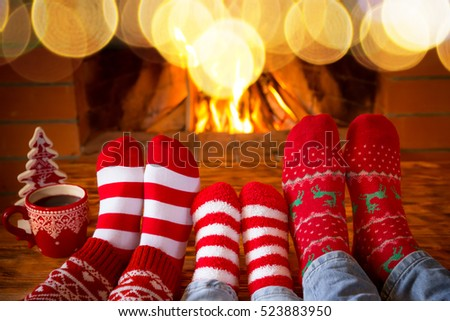 Family in Christmas socks near fireplace. Mother; father and baby having fun together. People relaxing at home. Winter holiday Xmas and New Year concept