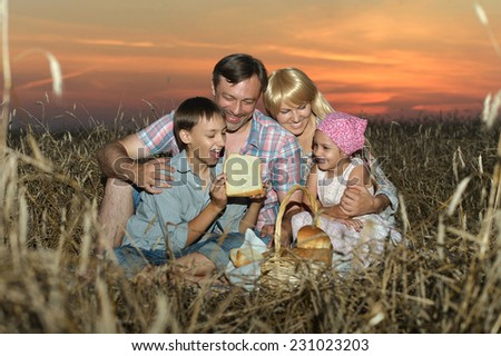 Family in field in sunset,reading a book