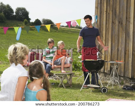 Family in garden having barbecue
