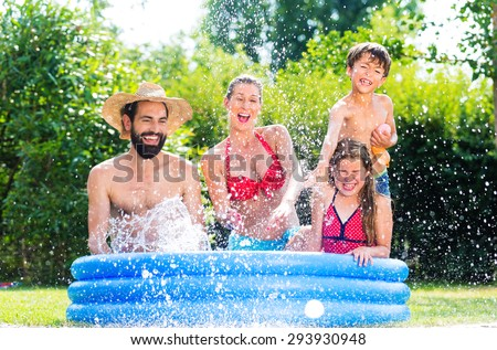 Family in garden pool cooling down by splashing water - stock photo
