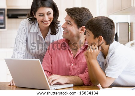 Family in kitchen with laptop smiling - stock photo