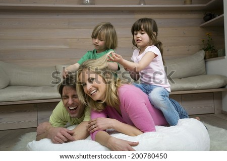 Family in living room children sitting on parent's back playing pulling parent's hair