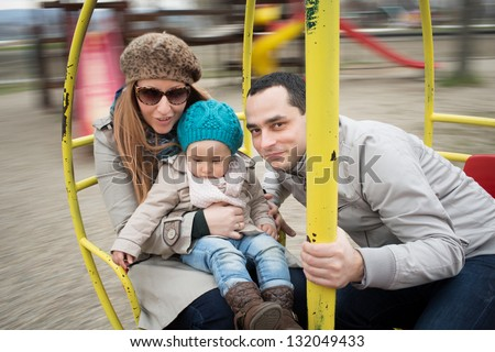 Family  in motion blur on a rotating swing with their daughter.
