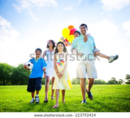 Family in outdoors walking towards a camera. - stock photo