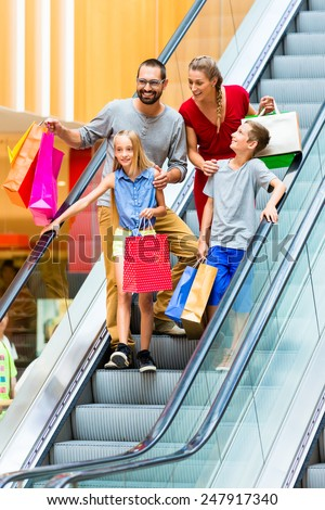 Family in shopping mall on escalators with bags - stock photo