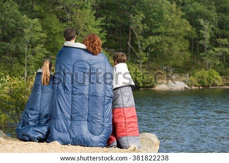 Family in sleeping bags by lake