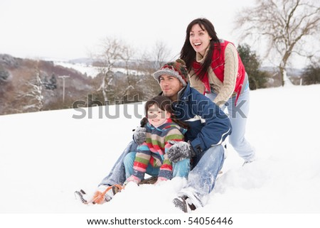 Family In Snow Riding On Sledge - stock photo