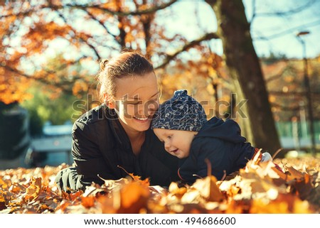 Family in the autumn park. Mom playing with son child in the autumn nature. Mom and her little baby child happy together.