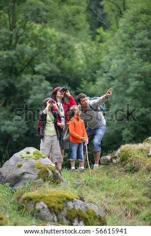Family in the countryside looking through binoculars - stock photo