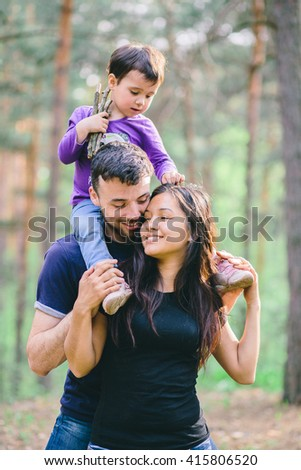 Family in the forest. Dad with a child on his shoulders hugging her mother - stock photo