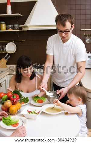 Family in the kitchen with some fruits and vegetables