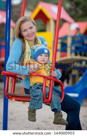 family in the park. child rides on a swing
