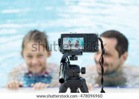 family in the pool, take video