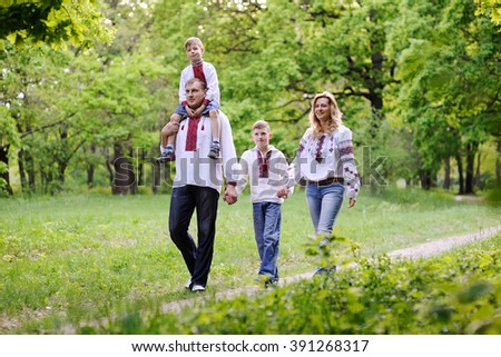 family in Ukrainian embroidered shirts are on a path in a forest