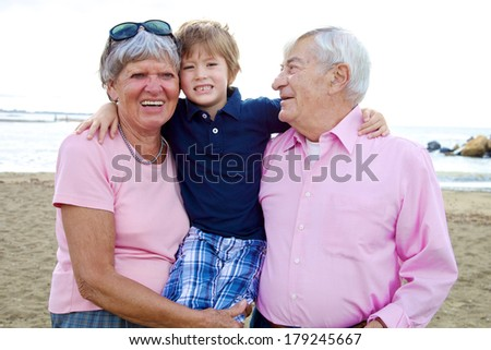 Family in vacation hugging child with grandma and grandpa
