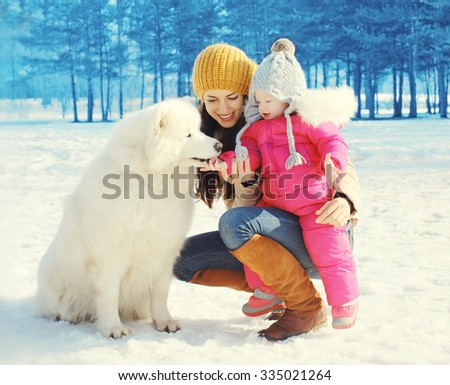 Family in winter day, happy mother and child walking with white Samoyed dog in park - stock photo