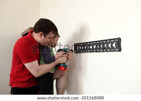 Family installing mount TV on the wall at home - stock photo