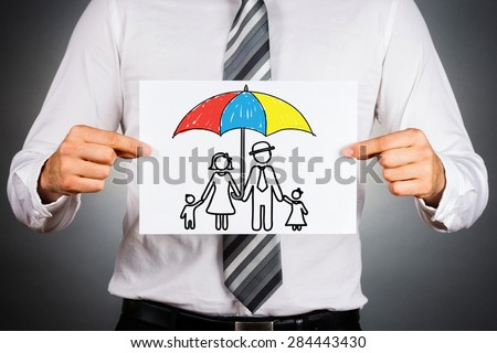 Family insurance concept. Businessman holding paper with drawing of a family under the umbrella.  - stock photo