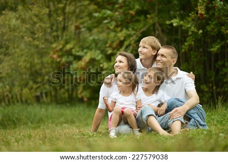 Family is having picnic in green summer park - stock photo