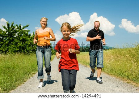 Family  jogging with her daughter; focus is only on the girl in front! - stock photo