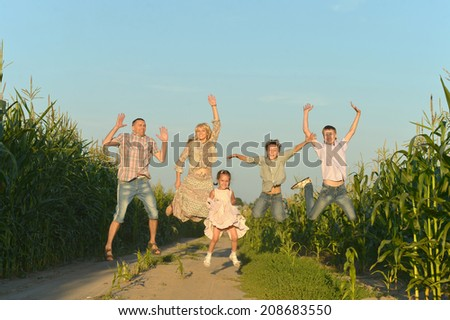 Family jumping on road in corn field - stock photo