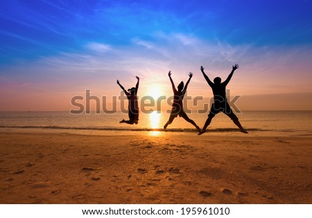 family jumping team on the beach on beautiful sunrise silhouette shot,happy family concept