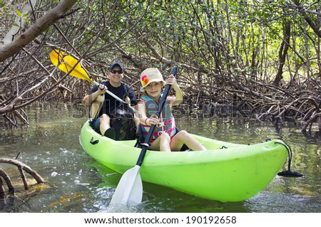 Family kayaking through tropical mangrove forest - stock photo