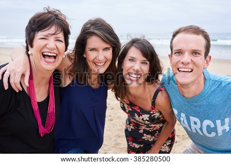 Family laughing and having fun on the beach together - stock photo