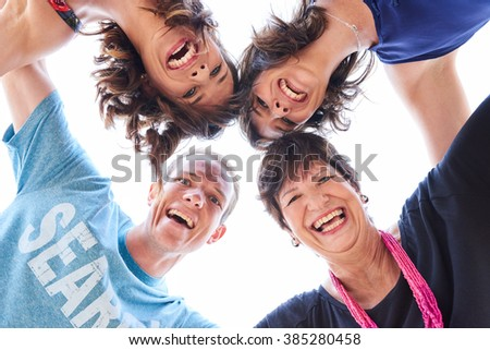 Family laughing and looking at the camera together - stock photo