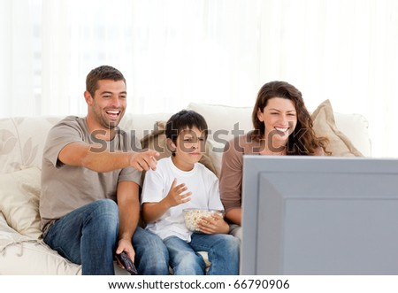 Family laughing while watching television together in the living-room - stock photo