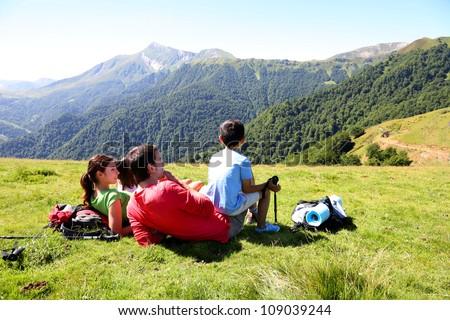 Family laying down the grass enjoying mountain view - stock photo