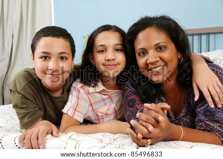 Family laying down together in a bed - stock photo