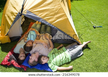Family laying in tent on lawn - stock photo