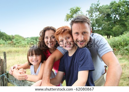 Family leaning on a fence