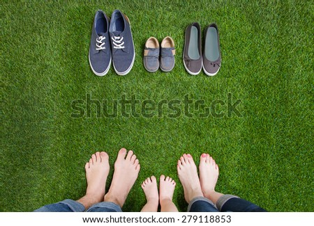 Family legs in jeans and shoes standing  on grass