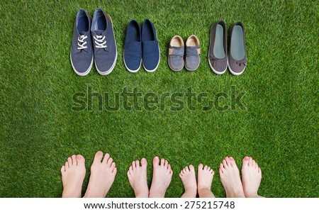 Family legs standing on green grass having fun outdoors in spring park with theirs shoes