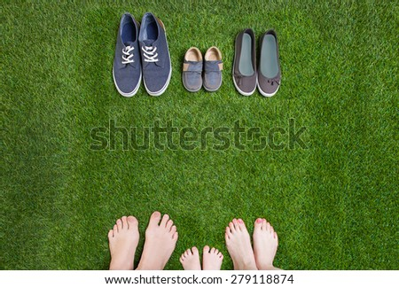 Family legs  standing  opposite shoes on  grass - stock photo