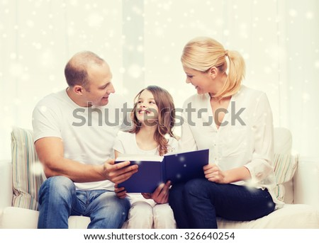 family, leisure, education and people - smiling mother, father and little girl reading book over snowflakes background - stock photo