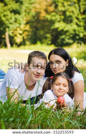 Family lie at meadow in a park