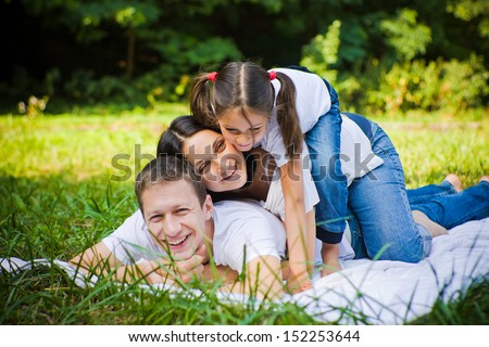 Family lie at meadow in a park. Fun - stock photo