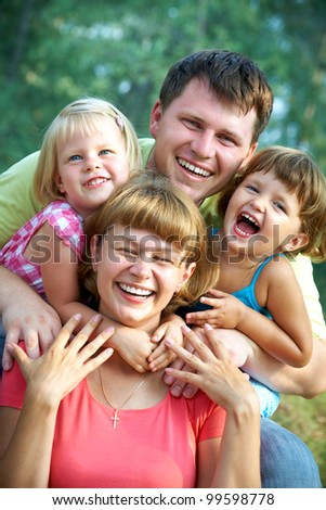 family lifestyle portrait of a mum and dad with their children having good time in the green  park - stock photo