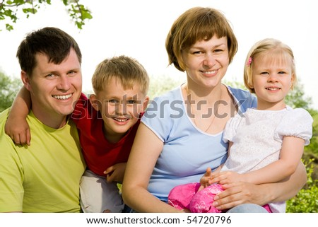 family lifestyle portrait of a mum and dad with their daughter and son  having good time - stock photo
