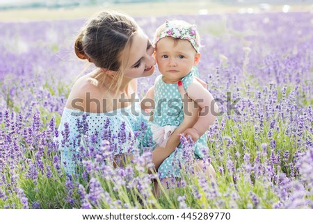 Family look happy mom is having fun with her baby girl in purple lavender field, summer time - stock photo
