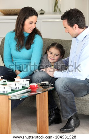 Family looking at a new-build model - stock photo