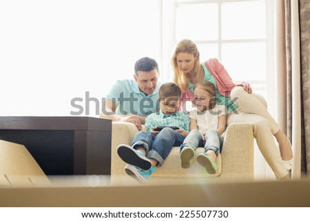 Family looking at boy playing hand-held video game at home - stock photo