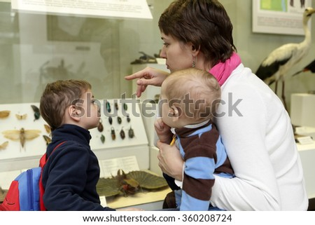 Family looking at insects in a museum - stock photo