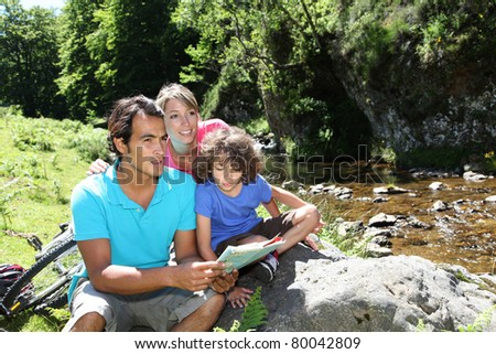 Family looking at map by mountain river - stock photo