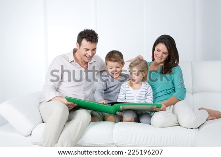family looking at pictures on green book