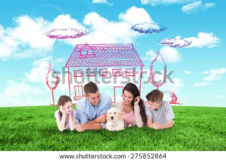 Family looking at puppy while lying against blue sky over green field - stock photo