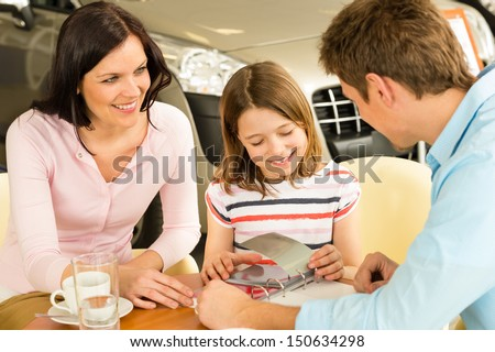 Family looking at shade cards in car showroom - stock photo
